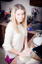 Sweet young pretty blond woman prepares dough in the kitchen happy smiling & looking at camera
