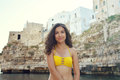 Sweet young woman wearing a bikini yellow enjoying her holiday in southern Italy rocky coast. Travel in Europe. Royalty Free Stock Photo