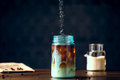 Sweetener Pouring Into Iced Organic Coffee Served In Blue Mason Jar