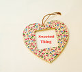 The sweetest thing heart shape decorated with flowers and in an open window message in red letters bright background Royalty Free Stock Photo