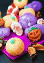 Sweets and candies for the holiday halloween focus on pumpkin in foreground Stock Photos