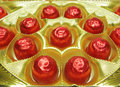 Sweets in red envelopment in gold box Stock Photo