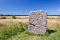 Swidish rune stone ancient with modern wind turbines in background Royalty Free Stock Photo