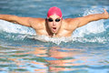 Swimmer athletic man swimming butterfly in a cap approaching the camera rising up out of the water male athlete fitness Stock Images