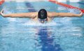Swimmer in cap breathing performing the butterfly stroke Royalty Free Stock Photo