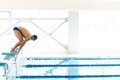 Swimmer jumping from starting block i Royalty Free Stock Photo