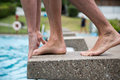 Swimmer standing on starting block at swimming pool man public ready to jump Stock Photo