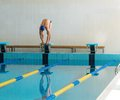 Swimmer standing on starting block young muscular in low position in a swimming pool Stock Photos