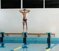 Swimmer standing on starting block young muscular in a swimming pool Royalty Free Stock Photography