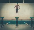 Swimmer standing on starting block young muscular in a swimming pool Stock Image