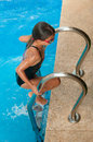 Swimmer - Young Girl Climbing Out Of Swimming Pool Royalty Free Stock Images