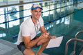 Swimming coach with stopwatch by pool at leisure center portrait of a the the Royalty Free Stock Photos