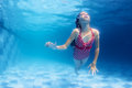 Swimming girl dives underwater in the blue pool Royalty Free Stock Photo