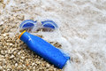 Swimming goggles and suntan lotion lying on pebble beach in wate Royalty Free Stock Photo