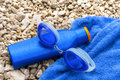 Swimming goggles, suntan lotion and towel on pebble beach. Royalty Free Stock Photo