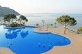 Swimming pool area near Mediterranean Sea in the morning Royalty Free Stock Photo