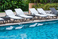 Swimming pool with beach chairs Royalty Free Stock Photos