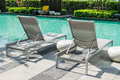 Swimming pool with beach chairs on deck Stock Photo