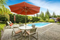 Swimming pool with deck chairs backyard and patio table umbrella Royalty Free Stock Images