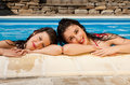 Swimming pool girl friends enjoying the hot sun in the Royalty Free Stock Image
