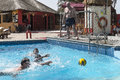 Swimming pool in hotel resort on the coast of the atlantic ocean gambia africa the men play water polo Stock Photo