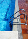Swimming pool ladder crystal clear blue water with Royalty Free Stock Photo