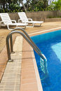 Swimming pool ladder and sunloungers from stainless steel material white Royalty Free Stock Images
