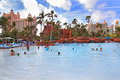 Swimming pool in paradise island the bahamas atlantis resort surrounded by palm trees Royalty Free Stock Image