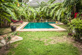 Swimming pool at private tropical villa backyard among tropical formal garden with palm trees and turquoise water Royalty Free Stock Photo