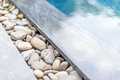 Swimming pool shining blue water sun glare bordered natural pebble path framed stone decoration design pools relaxation spa Royalty Free Stock Photos