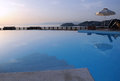 Swimming pool at sunrise view of the and the sea and sky in the background on crete island in greece Royalty Free Stock Photos