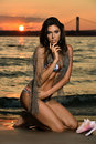 Swimsuit model posing at ocean beach location wearing sexy bikini and fishnet Royalty Free Stock Photo