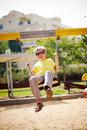 On the swing boy in sunglasses having fun a Royalty Free Stock Image