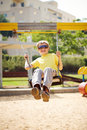 On the swing boy in sunglasses having fun a Royalty Free Stock Photos