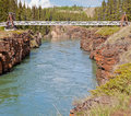Swing bridge across miles canyon of yukon river rock cliffs with suspension just south the city whitehorse territory canada Royalty Free Stock Image