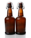 Swing top beer bottles with condensation closeup of two cold brown covered vertical format on white reflection Royalty Free Stock Image