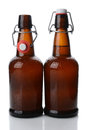 Swing top beer bottles one open closeup of two cold brown covered with condensation bottle is vertical format on white with Stock Photography