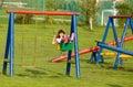 Swinging happy little girl on playground area Stock Photography