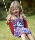 Swinging little girl on swing set Royalty Free Stock Photo