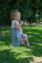 Swinging little girl on tree swing Royalty Free Stock Photos