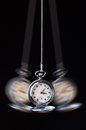 Swinging pocket watch hypnosis on black Royalty Free Stock Photo