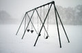 Swings covered with snow in the playground Royalty Free Stock Images