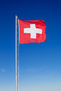 Swiss flag on metal pole the national of switzerland flying a against a clear blue sky Stock Image