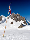 Swiss flag in the mountains jungfraujoch pass alps Royalty Free Stock Images