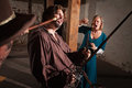 Swordsman is hit with a mace during fight as women screams Stock Photos