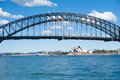 Sydney harbor bridge and opera house a view of the from the water with the blue sky with white clouds Stock Photography
