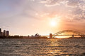 Sydney harbor bridge and opera house a view of the from the water with the at sunset Royalty Free Stock Images