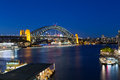 Sydney harbour bridge at dusk boat traffic around rush hour on a winter s evening in australia Royalty Free Stock Photo