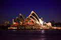 Sydney opera house at night with city lights in the background and harbour in the foreground Stock Photography