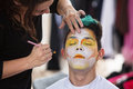 Sylist putting makeup on clown young male getting face Stock Photos
